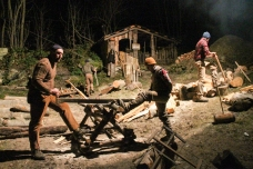 "TAGLIALEGNA/WOODCUTTERS-LUMBERJACKS: Daniele Somà, Emanuele Basso and Gabriele Dho play the woodcutters-luberjacks. Behind them, more logs sent by woodcutters working on the hill above come down through a wire fixed to a big wooden stake. Woodcutters above can be heard shouting from time to time ""Alla vita!"" (Be careful!), to which workers at the foot of the hill respond ""Campa!"" (Throw it down!), communicating that there is no danger and that everybody will keep safe and away from the descending logs. (Gianluca Avagnina Photography)"