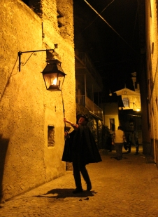 LANTERNIERE/LAMPLIGHTER: Lamplighter Ezio Dho extinguishes a gas streetlamp in Prea at the end of the event. He is in charge of both the lighting and extinguishing of all the streetlamps in the village. To recreate the atmosphere of the 17th century, the organisers prohibited the use of electricity for the entire duration of the Living Crib. In the background, behind Mr Dho, the façade of the Parochial Church can be seen. (Gianluca Avagnina Photography)